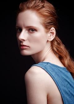 Modelltest mit tragendem t-shirt des jungen schönen mode-modells auf schwarzem hintergrund