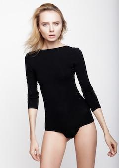 Modellversuche des jungen hübschen blonden mädchens über weißem hintergrund