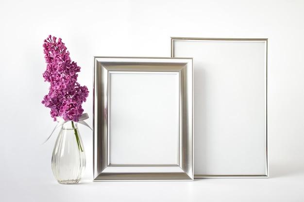Modellvorlage mit zwei leeren silbernen rahmen und rosa lila blumenzweig in glasvase auf weißem hintergrund.