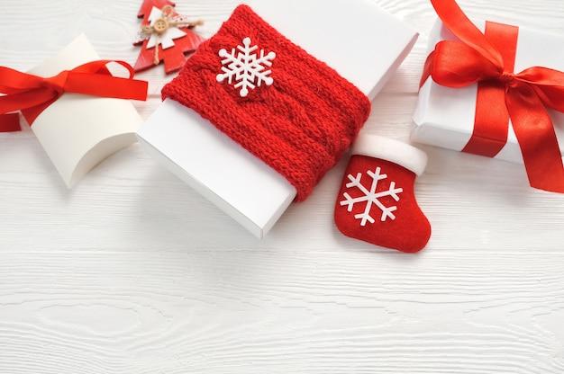 Modellweihnachtshintergrund mit dekorationen und geschenkboxen und roter bogen