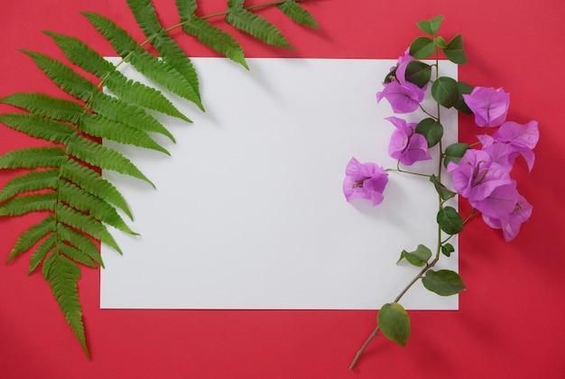 Modellweißbuch mit platz für text auf rotem hintergrund und tropischen blättern und blumen.