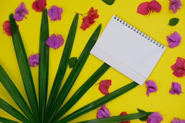 Modellweißbuch mit platz für text oder bild auf gelbem hintergrund und tropischem palmblatt und blume.