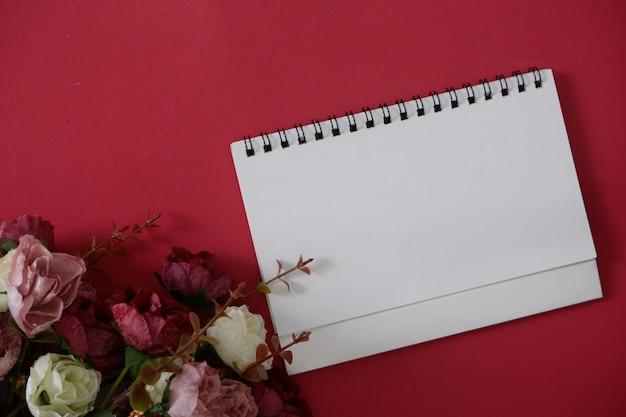 Modellweißbuch mit platz für text oder bild auf rotem hintergrund und blume.