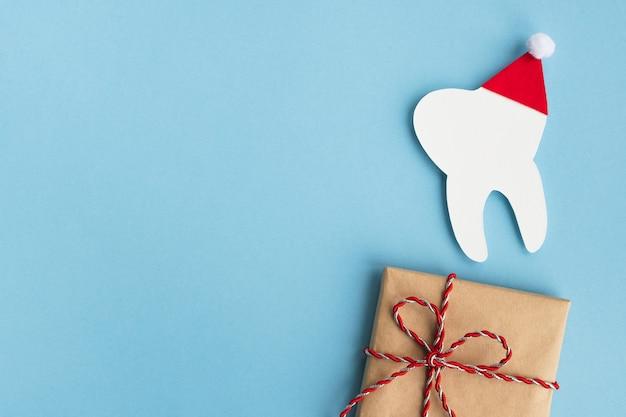 Modellzahn in einer roten weihnachtsmannmütze und geschenk. medizinische winterpostkarte für die zahnmedizin