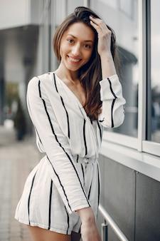 Modemädchen, das in einer sommerstadt steht