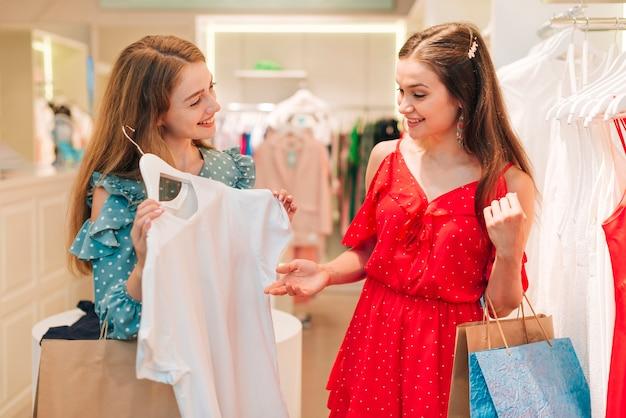 Modemädchen, die im geschäft kleidung überprüfen