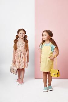 Modemädchen in der stilvollen kleidung auf farbiger wand