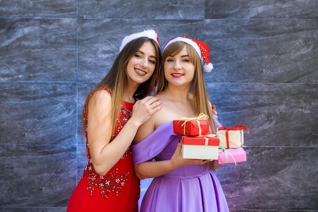 Modemädchen in eleganten abendkleidern, die mit geschenkboxen posieren. neujahrsfeier konzept