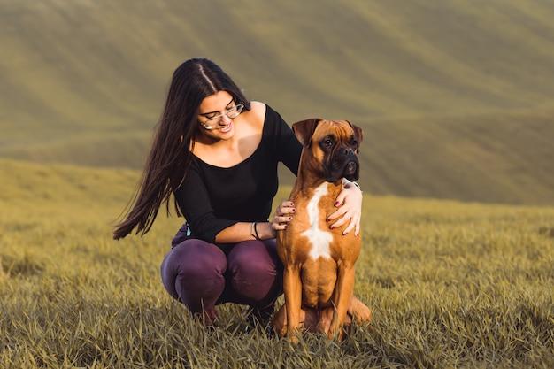 Modemädchen mit ihrem boxerhund an der wiese im fall