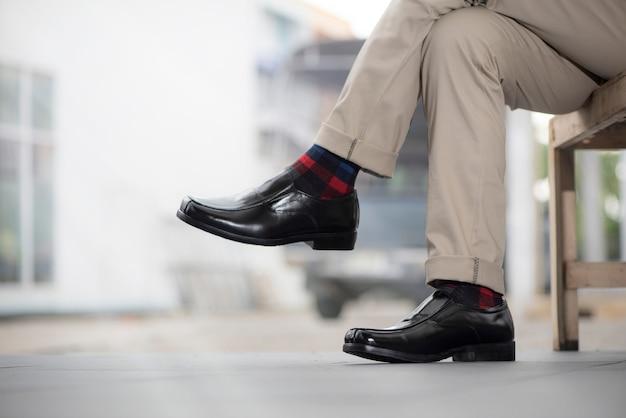Modemann, der schwarze lederschuhe trägt