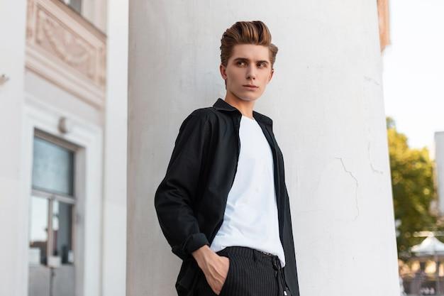 Modemann in stilvollen kleidern geht auf der straße