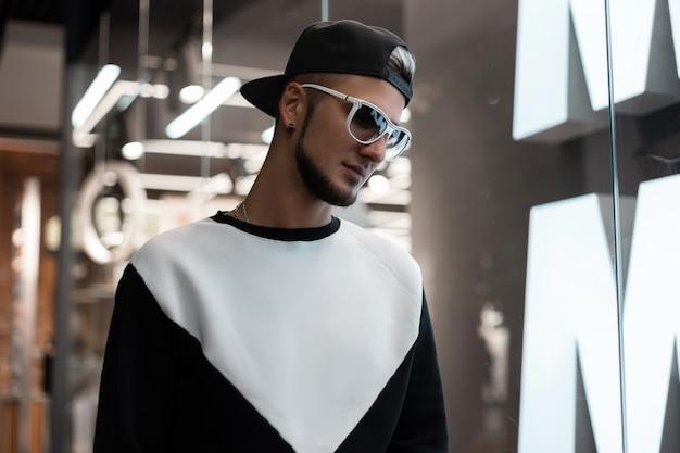 Modemann mit sonnenbrille in stilvoller oberbekleidung drinnen Premium Fotos