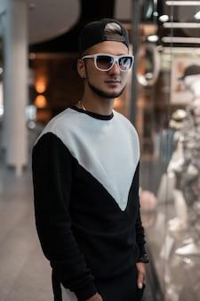 Modemann mit sonnenbrille in stilvoller oberbekleidung drinnen
