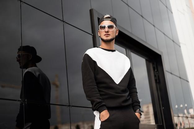 Modemann mit sonnenbrille und mütze im sweatshirt geht in die stadt