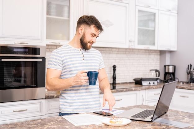 Modemmann, der beim frühstück arbeitet
