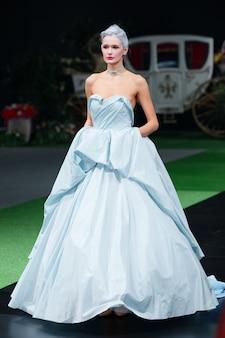 Modemodell im designerkleid, das auf landebahn geht
