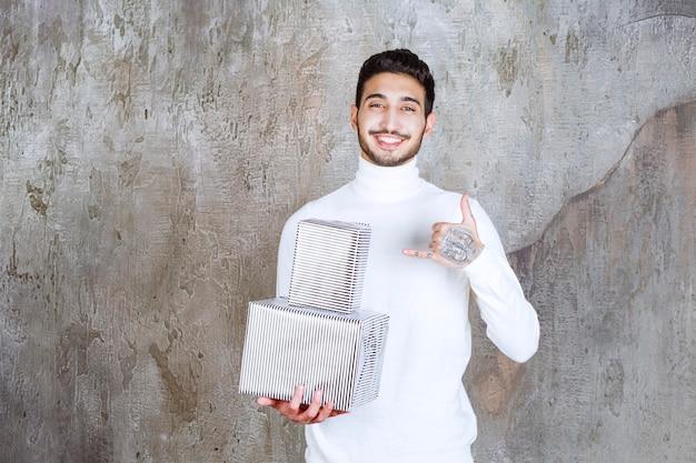 Modemodell im weißen pullover, der zwei silberne geschenkboxen hält und positives handzeichen zeigt.