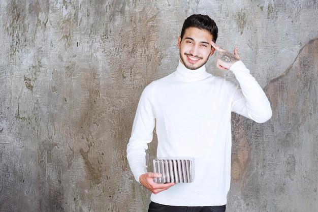 Modemodell im weißen pullover mit einer silbernen geschenkbox, sieht verwirrt und nachdenklich aus