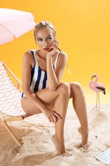 Modemodell mit hand auf gesicht wirft auf gelbem hintergrund auf