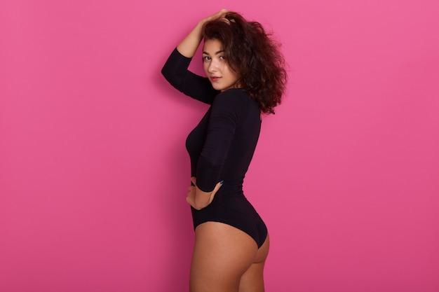 Modemodell posiert isoliert auf rosa tragendem schwarzen kombikleid, stehend mit hand eins auf ihrem kopf und anderem auf hüfte, seitenansicht der schlanken frau mit dunklem welligem haar.