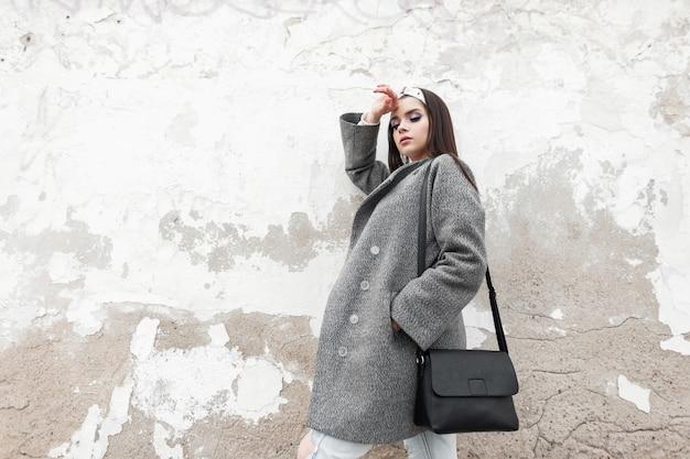 Modemodell süße frau in grauem elegantem mantel in glamourösem bandana mit stilvoller schwarzer tasche entspannt sich in der nähe der weißen vintage-wand in der stadt. wunderschönes mädchen in lässiger oberbekleidung genießt den frühlingstag auf der straße im freien