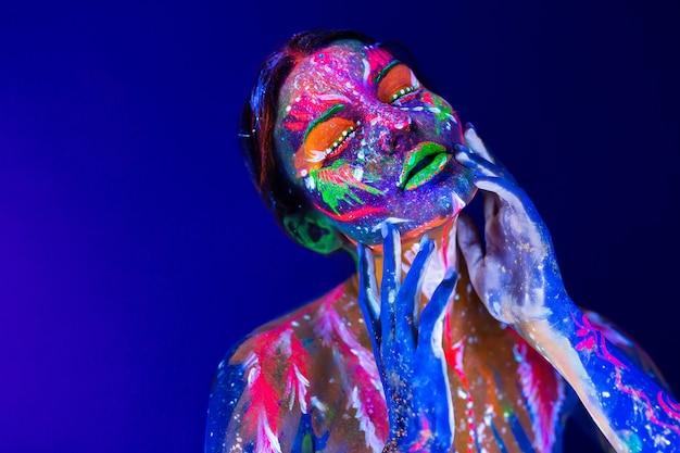 Modemodellfrau im neonlicht mit fluoreszierendem make-up.