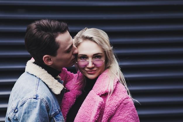 Modepaar, das in stadtumgebungen umarmt