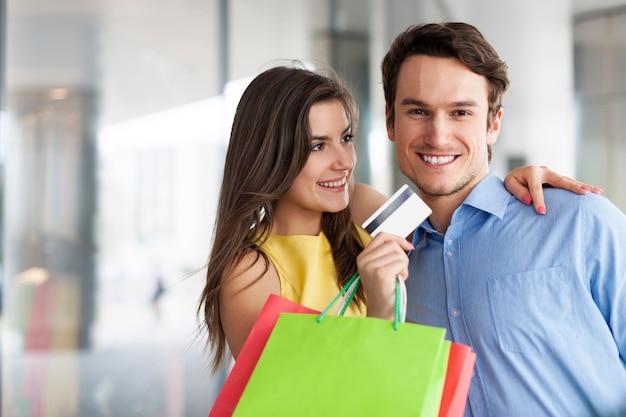 Modepaar mit kreditkarte und einkaufstaschen
