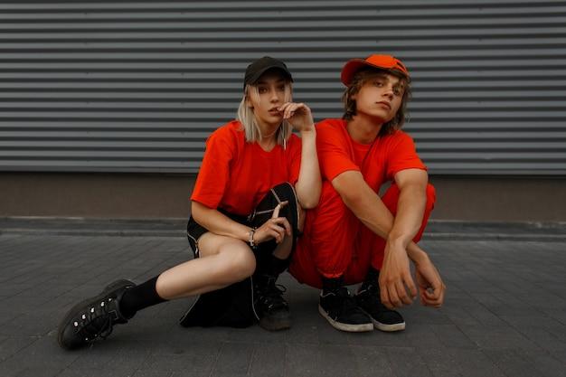 Modepaar mit modischen mützen in orangefarbenen stilvollen kleidern mit turnschuhen, die nahe der grauen metallwand sitzen