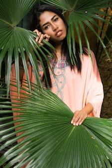 Modeporträt der atemberaubenden asiatischen frau, die im tropischen garten aufwirft. trägt boho-kleid und stilvolle accessoires.