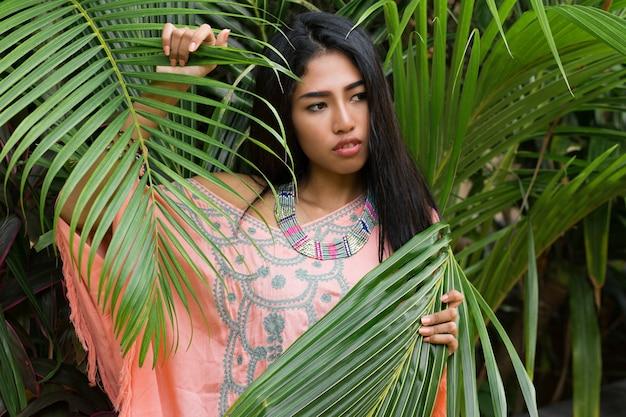 Modeporträt der attraktiven asiatischen frau, die im tropischen garten aufwirft. trägt boho-kleid und stilvolle accessoires.