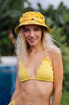 Modeporträt der blonden kaukasischen frau im gelben bikini und im panama am rand des blauen schwimmbades