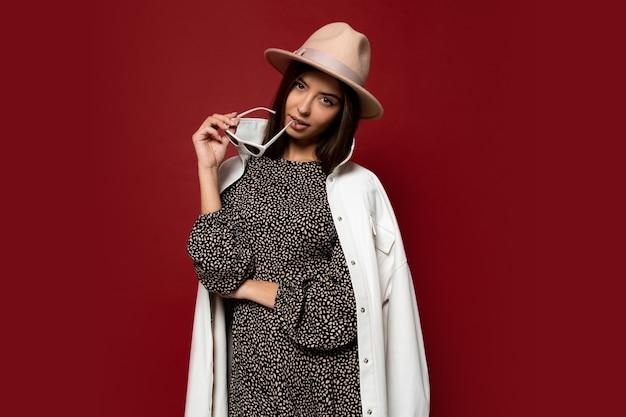 Modeporträt der eleganten brünetten frau mit gekleidetem weißem mantel und beigem hut, der sonnenbrille hält. trendiger modestil für herbst oder winter.