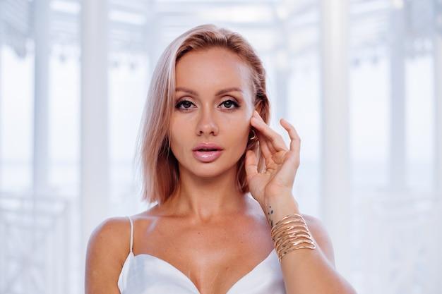 Modeporträt der europäischen blonden frau im goldenen armband und in den ohrringen des seidenweiß-sommerromantikkleides