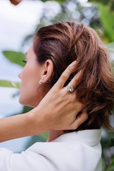 Modeporträt der frau an der tropischen luxusvilla, die weißen stilvollen blazer und schmuck über tropischen blättern trägt