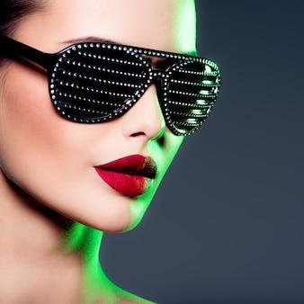 Modeporträt der frau, die schwarze sonnenbrille mit diamanten trägt. gesättigte farben