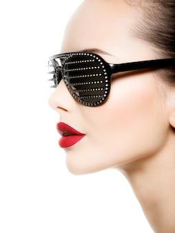 Modeporträt der frau, die schwarze sonnenbrille mit diamanten und roten lippen trägt