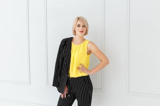 Modeporträt der frau im gelben und schwarzen anzug