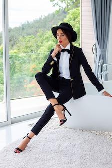 Modeporträt der frau im schwarzen anzug, in der schmetterlingskrawatte und im hut an der luxusvilla
