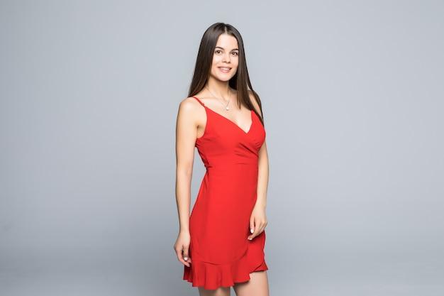 Modeporträt der frau mit den langen haaren im roten kleid lokalisiert auf grauer wand.