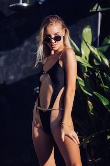 Modeporträt der gebräunten jungen stilvollen europäischen frau der passform im schwarzen trendigen badeanzug