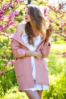 Modeporträt der glückseligen atemberaubenden eleganten frau, die im park mit blühenden sakura-bäumen zur frühlingszeit aufwirft
