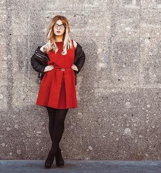 Modeporträt der hippie-frau im stilvollen lässigen sommeroutfit, das gegen wandhintergrund aufwirft.