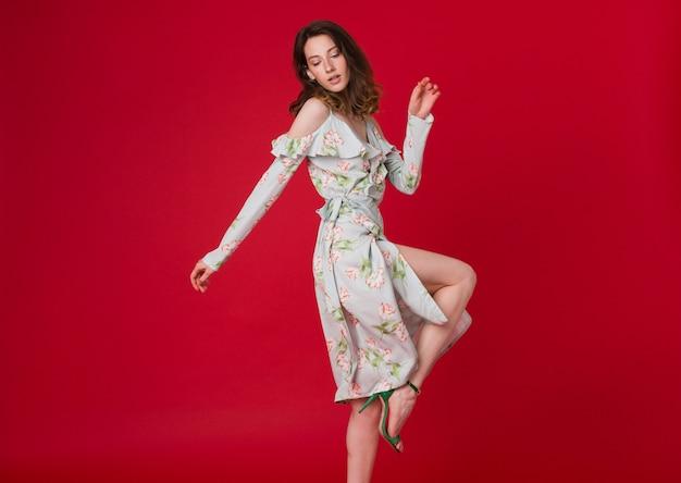 Modeporträt der hübschen jungen frau im blau bedruckten kleid auf rotem studio