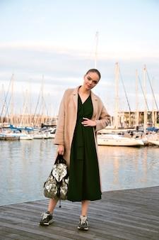Modeporträt der jungen atemberaubenden eleganten frau, die promenade aufwirft, kleidermantel-turnschuhe und rucksack, luxus-tourist, weiche warme farben trägt.