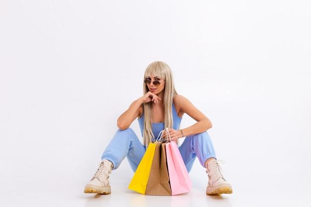 Modeporträt der jungen blonden frau mit dem langen herrlichen glatten haar mit den bunten einkaufstaschen im studio auf einem weiß.