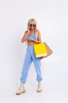 Modeporträt der jungen blonden frau mit langen herrlichen geraden haaren halten bunte einkaufstaschen