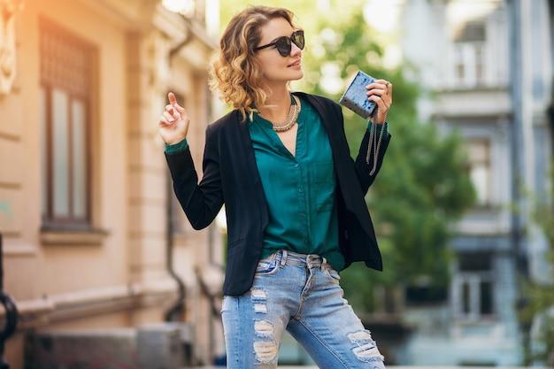 Modeporträt der jungen eleganten frau, die in der straße in der schwarzen jacke, in der grünen bluse, in den stilvollen accessoires, im halten der kleinen geldbörse, im tragen der sonnenbrille, im sommerstraßen-modestil geht