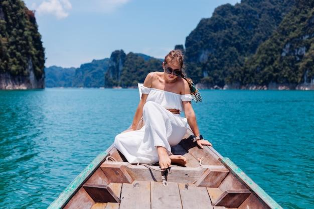 Modeporträt der jungen frau im weißen oberteil und in den hosen im urlaub, auf dem segeln des thailändischen holzboots. reisekonzept. frau im khao sok nationalpark.