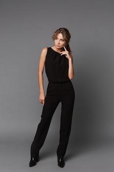 Modeporträt der jungen frau in voller länge in einer schwarzen freizeitkleidung auf dem grauen hintergrund